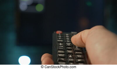 Close up man hand holding the TV remote control and changing channels.