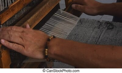 Close up man hands weave canvas with antique loom handweave...