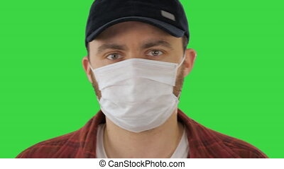 Man in black baseball cap with a medical mask on his face on a Green Screen, Chroma Key.