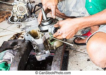 close-up, man repairing engine motorcycle