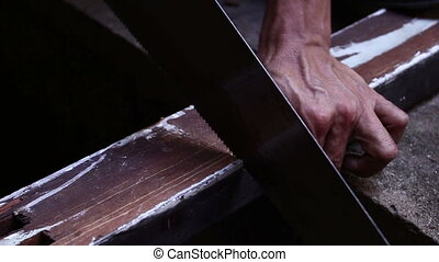 Man Sawing A Piece Of Wood - close up Man Sawing A Piece Of...