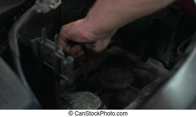 Close up man screwing car engine screws. Car service worker repairing and fixing a car motor.