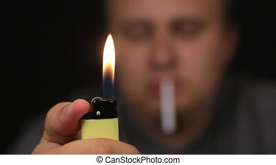 Close-up, man sets a gas lighter on fire. Focus on the lighter.