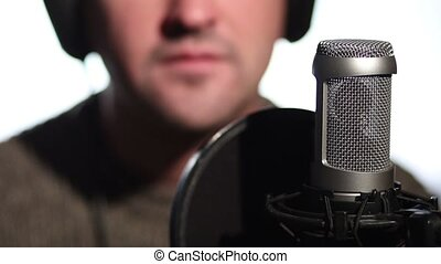 Close up man singing into a condenser microphone.