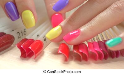 Close up manicured hands and nail color samples. Female...