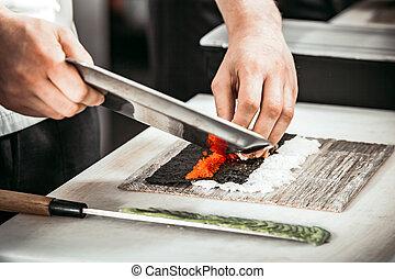 Close-up man`s hands making rolls in restaurant.