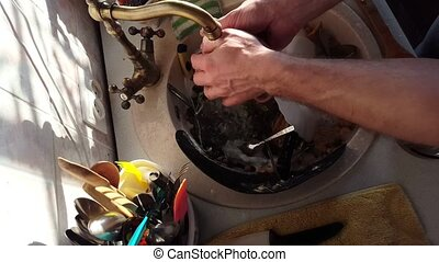 close-up mans hands washes a dishes, water jet rinses the...