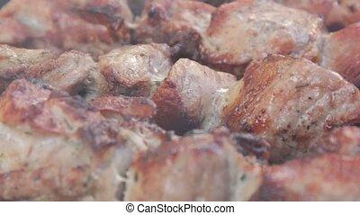 Close-up marinate shashlyk on a barbecue. Smoke over roast...