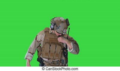 Close up. Marine walks, holds a radio station and gives orders on a Green Screen, Chroma Key. Professional shot in 4K resolution. 048. You can use it e.g. in your medical, commercial video, business, presentation, broadcast