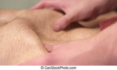 Close-up massage of the diaphragm and placement of organs in the abdominal cavity of a male athlete by a physiotherapist. Alternative medicine.
