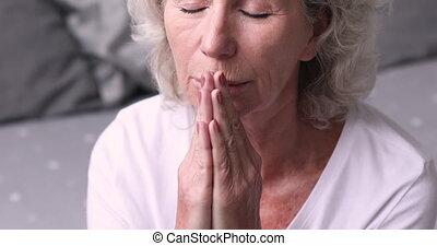 Close up mature older woman saying morning worship after ...