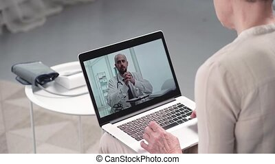 mature woman asking questions to her doctor in a video chat.