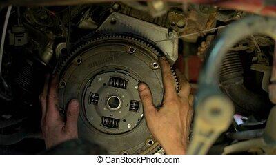 Close up mechanic installing and adjusting car clutch. ...
