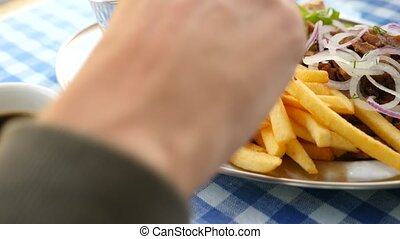 close-up, men's hands eat Greek souvlaki. dips a piece of...