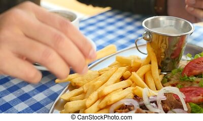 close-up, men's hands eat Greek souvlaki. dips a piece of French fries into a white sauce. 4k, slow motion