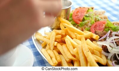 close-up, men's hands eat Greek souvlaki. dips a piece of...