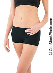 Close-up mid section of a fit woman in sportswear