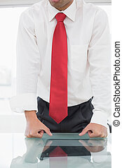 Close-up mid section of a well dressed businessman with clenched fists on the desk at office