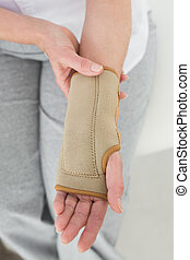 Close-up mid section of a woman with hand in wrist brace