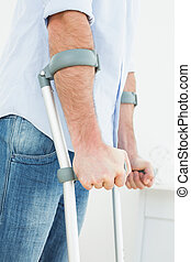Close-up mid section of a young man with crutches