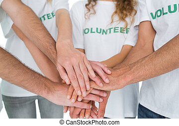 Close-up mid section of volunteers with hands together over white background