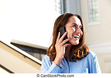 Close up middle aged woman smiling and talking on cell phone outdoors