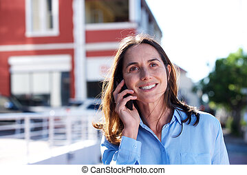 Close up middle aged woman smiling and talking on mobile phone outdoors