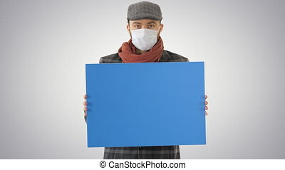 Close up. Mockup blue screen. Man in a trendy outfit and medical mask holding blank placard on gradient background. Professional shot in 4K resolution. 53. You can use it e.g. in your medical, commercial video, business, presentation, broadcast
