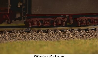 Close up model of toy locomotive moving on railroad. Vintage...