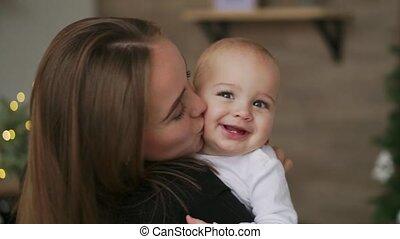 close-up, moederschap, vrolijke , vertragen, keuken, mooi, eva, moederschap, mother., kerstmis, mamma, omhelzingen, geliefd, moeder, liggen, stander, glimlachen, kussende , zijn, het kijken, motie, garlands, hugging., beeldmateriaal, baby, video, achtergrond, samen, kind, gezin, concept, bomen., witte