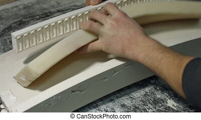 Close up molding a gypsum cornice. Mans hands holding...
