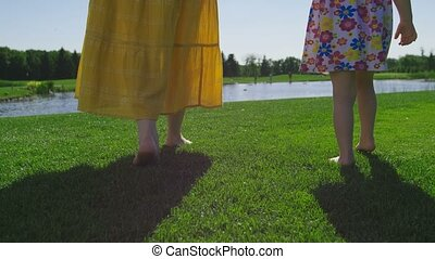 Close-up mom and daughter legs walking on grass