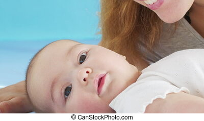 Close up mother gently kissing baby enjoying loving mom playfully caring for toddler at home sharing connection with her newborn child, healthy childcare