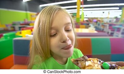 Close-up motion of girl eating pizza at entertainment...
