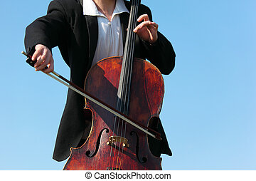 close-up musician plays violoncello against sky