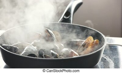 Close up mussels cooking in a hot pan.