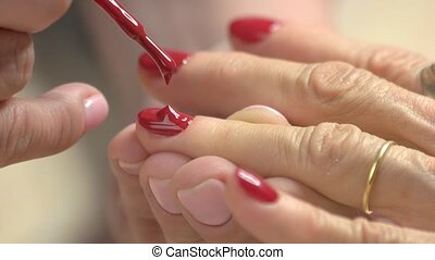 Close up nail painting with red lacquer. Manicurist is...