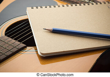 close-up Notebook and pencil on guitar, Writing music