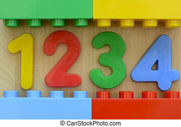 Close up of 1 2 3 4 in plastic numbers surrounded by plastic toy blocks