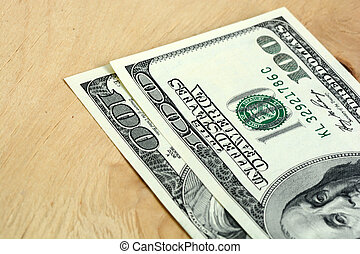 Close-up of a 100 dollars banknotes on wooden background