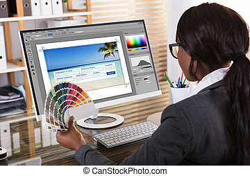 Female Designer Holding Colorful Swatch Working On Computer