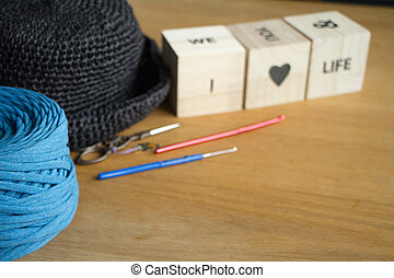 Close up of a ball of bright blue yarn, a black knitted hat and wooden cubes with an inscription in English I love life on a light wooden surface. Selective soft focus.