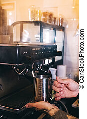 Close-up of a barista preparing coffee. The process of making cappuccino in a coffee machine. Measuring cup in hand. The hot drink is poured into a paper cup. Takeaway food