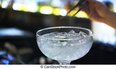 Close up of a bartender adding lime slices into a cocktail