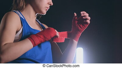 Close-up of a beautiful athletic female boxer pulls red bandages on the hands of a female fighter. steadicam shot