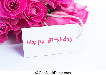 Close up of a beautiful bouquet of pink roses with a happy birthday card on a white table
