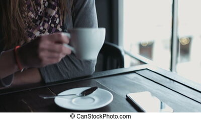 Close-up of a beautiful female in her 20s sitting at the cafe and sipping drink from the cup. Girl drinking tea or coffee indoors.