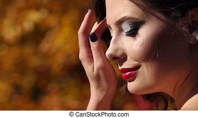 Close-up of a beautiful girl with bright make-up walking in autumn park.
