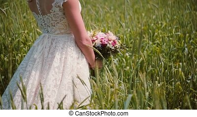 Close-up of a beautiful lacy wedding dress on a bride standing in a wheat field with a bouquet in her hands.