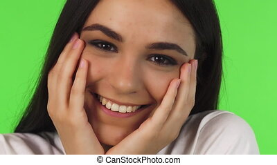 Close up of a beautiful teenage girl smiling cupping her face with her hands